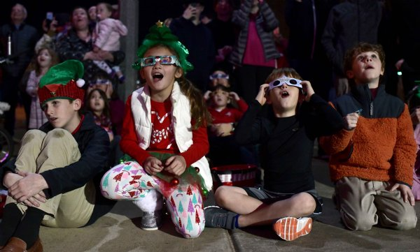 """From left to right, Evan Palmer,13, son of Heather and Bobby Palmer, Annabelle Brislin, 8, daughter of Amber and Quinn Brislin, John Davis Clark, 7, son of Hope and Brian Clark, and Charles Glenn, 7, son of Robby and Frances Glenn, watch in awe as Mayor Robert E. Smith, Sr. turned the lights on for the Christmas tree Dec. 5 at the Columbus Riverwalk. """"Wow,"""" the kids exclaimed as they peeked through their 3D glasses. / Photo by: Jennifer Mosbrucker/Dispatch Staff"""