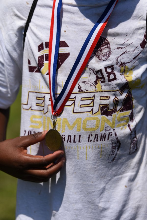 A player holds his medal after the Jeffery Simmons Football camp on Friday at the Starkville Sportsplex in Starkville. At the end of the camp on Friday one notable athlete from each grade was awarded a trophy and every participant received a medal. Kids also got to-go lunches after the camp. / Photo by: Claire Hassler/Dispatch Staff