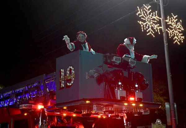 Santa and Mix Claus wave from the bucket of a Columbus Fire Department truck during the Christmas parade Dec. 2 along Main St. / Photo by: Jennifer Mosbrucker/Dispatch Staff
