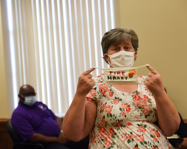 """Rebecca Bailey shows people a mask she made that has """"Fire Harry"""" written on it during the Lowndes County Board of Supervisors meeting on Wednesday at the Lowndes County Courthouse. Bailey lives in district 1of Lowndes County, which is Supervisor Harry Sanders' district. Bailey asked Sanders to resign because of his racist beliefs. Bailey also said the Columbus-Lowndes Public Library asked her to donate her mask to their archives documenting the removal of the Confederate monument from the courthouse lawn. / Photo by: Claire Hassler/Dispatch Staff"""