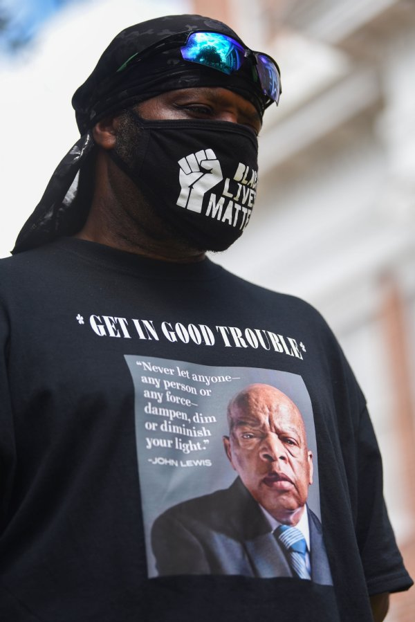 Local Activist Johnny Hampton wears a shirt honoring Civil Rights Activist John Lewis, who died on July 17, during the Equality and Justice March on Saturday in Columbus. Hampton spoke about Lewis during his speech at the event, saying Lewis died knowing that a new youth movement has begun. / Photo by: Claire Hassler/Dispatch Staff