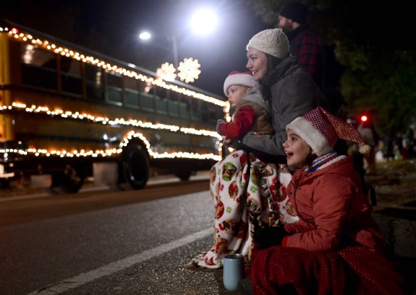 "Rhyn Wilson, 8, watches the Christmas parade with her parents Nathan and Elise Wilson, and little brothers Rhys Wilson, 5, and Riley Wilson, 1, Dec. 2 in Columbus. ""It's the grinch,"" she yelled as the Zion Church float went by a moment later. / Photo by: Jennifer Mosbrucker/Dispatch Staff"