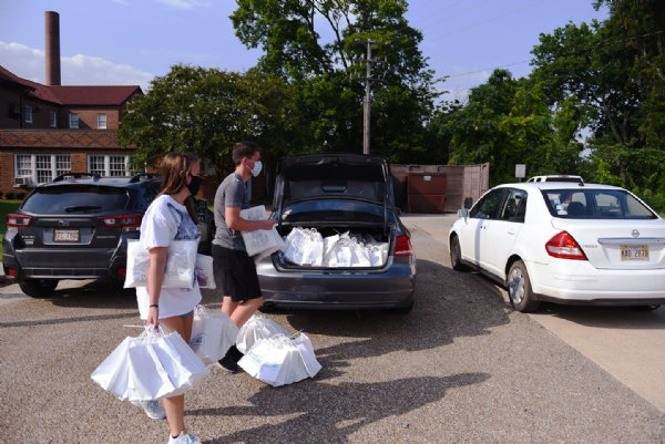 Ellie Holt and Ben Clark load bags of PPE and other welcome supplies for incoming students into cars on Wednesday outside Herbert Hall on the MSU campus in Starkville. Dante Hill, Associate Director of Resident Education said 800 students will be moving in each day next week. Each student will have a designated time slot in order to keep students spread out and each student will have a health screening before unloading their cars. / Photo by: Claire Hassler/Dispatch Staff