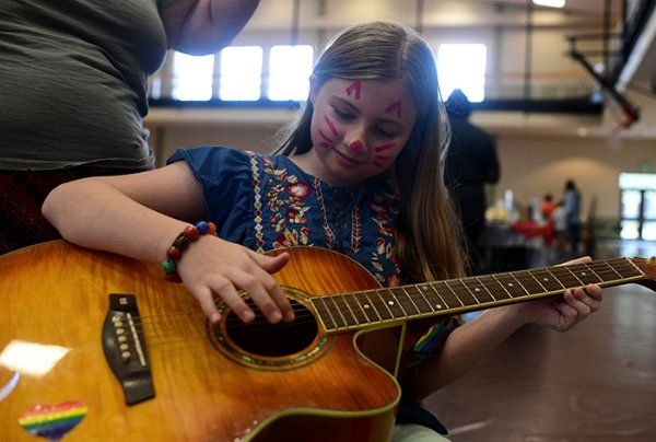 Cameron Long-McMillen, 9, plays local musician Georgia Graham's guitar during Art in the Park  Oct. 26 at the Starkville Sportsplex. This was her first time playing the guitar. / Photo by: Jennifer Mosbrucker/Dispatch Staff