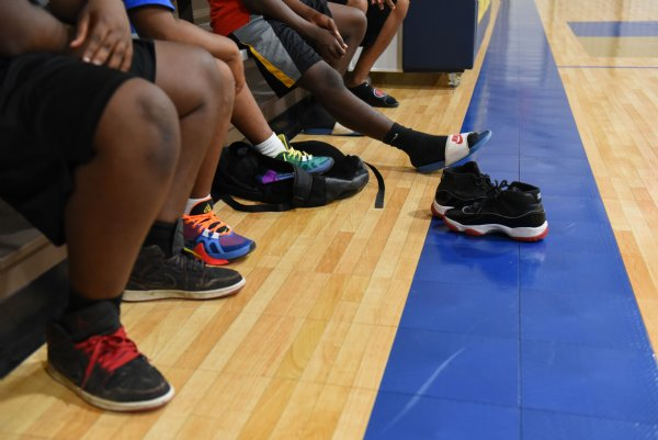 Kids and extra basketball shoes sit on the sidelines on Thursday at the Crawford Community Center. After over a year of dealing with a leaky roof and ripped up floor, the Crawford Community Center had its grand reopening on Monday. / Photo by: Claire Hassler/Dispatch Staff