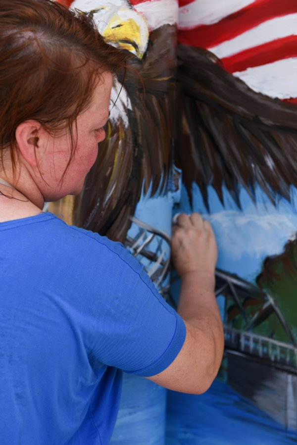 """Amy Ballard adds clouds to her painting on the utility box at the intersection of Main Street and 6th Street on July 16 in Columbus.  """"We all need to be more united,"""" Ballard said of what inspired her design. / Photo by: Claire Hassler/Dispatch Staff"""