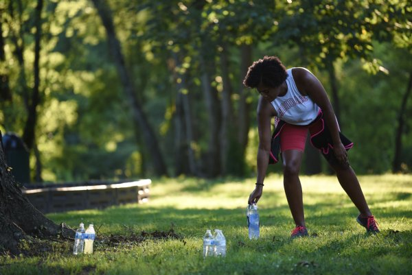 Ashley Dumas puts down her water after getting a drink during a Zumba class on Tuesday evening at the River Walk Soccer Complex in Columbus. Bonnie Partridge, who led the class, said doing Zumba outside does get pretty hot, and she won't miss the heat when they're back in the gym. / Photo by: Claire Hassler/Dispatch Staff