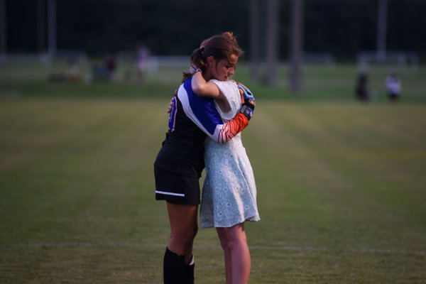 8th grader Chandler Nettles hugs Assistant Coach Noa Katherine Hardin after losing against Hartfield Academy on Tuesday in Starkville. / Photo by: Claire Hassler/Dispatch Staff