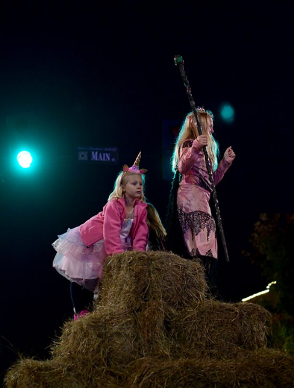 Andley Pylate, 10, and her sister Leni Ruth Pylate, 6, stand on top of the straw bales at the intersection of Main and Lafayette streets during Pumpkinpalooza Thursday night in downtown Starkville. The girls danced to music played by Thurlow's Party to Go as their mom recorded their dance moves. / Photo by: Jennifer Mosbrucker/Dispatch Staff