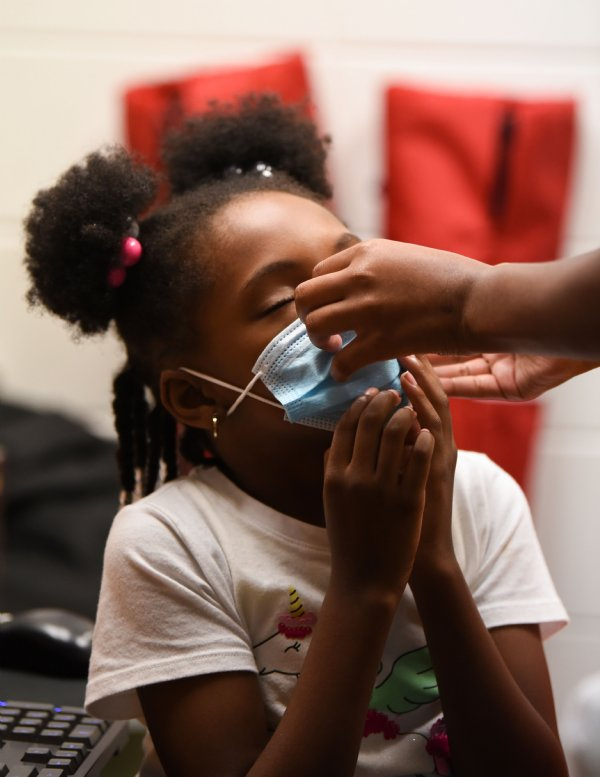 An older student helps Khloe Neely, 8, adjust her mask during Ms. Smith's Academic Summer Camp on July 21 at the Needmore Center in Starkville. As precautions for COVID-19, everyone wore masks throughout the day, except during lunch time, and people received hand sanitizer and got their temperature checked as they entered the building each morning. / Photo by: Claire Hassler/Dispatch Staff