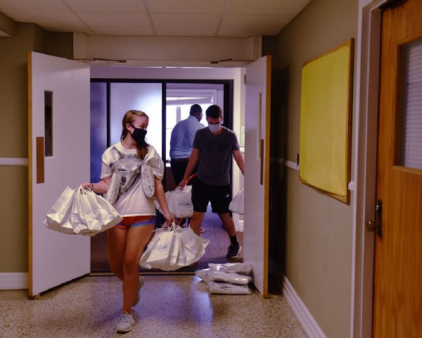 Ellie Holt and Ben Clark carry bags with PPE to cars on Wednesday at Herbert Hall on the MSU campus in Starkville. Resident Life has assembled one bag for each campus resident along with some extras, totaling at 4,800 bags, according to Dante Hill, Associate Director of Resident Education. / Photo by: Claire Hassler/Dispatch Staff