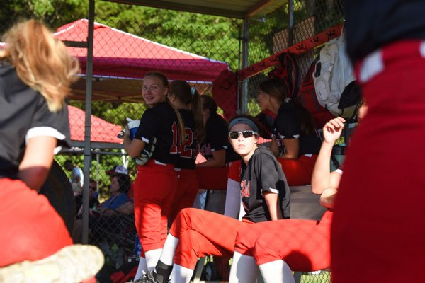 Players on the Oak Hill Academy softball team talk in the dugout during a game against Heritage Academy on Monday at Oak Hill Academy in West Point. / Photo by: Claire Hassler/Dispatch Staff